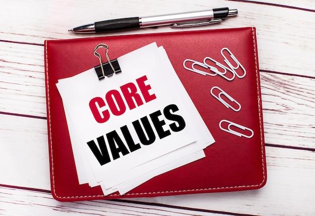 На светлом деревянном фоне бордовая ручка и блокнот. на блокноте есть белые скрепки и белая бумага с текстом основные ценности. бизнес-концепция