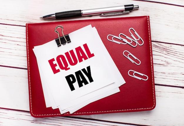 На светлом деревянном фоне бордовая ручка и блокнот. на блокноте есть белые скрепки и белая бумага с надписью equal pay. бизнес-концепция