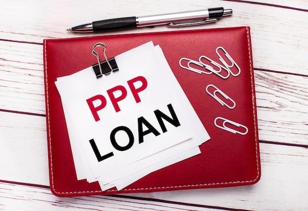 На светлом деревянном фоне бордовая ручка и блокнот. на блокноте есть белые скрепки и белая бумага с текстом ppp loan. бизнес-концепция