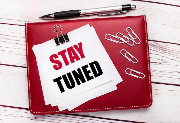На светлом деревянном фоне бордовая ручка и блокнот. на записной книжке есть белые скрепки и белая бумага с надписью stay tuned. бизнес-концепция