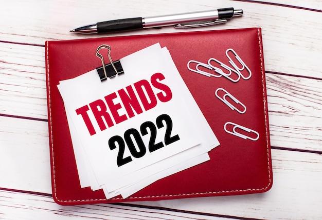 На светлом деревянном фоне бордовая ручка и блокнот. на блокноте есть белые скрепки и белая бумага с текстом тенденции 2022. бизнес-концепция