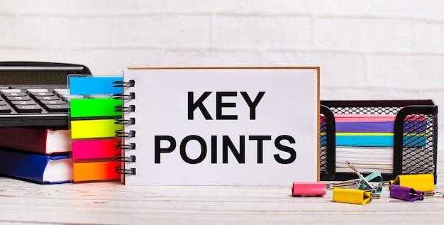 明るい木製の背景に、電卓、マルチカラーのスティック、「keypoints」というテキストが書かれたノートブック。ビジネスコンセプト