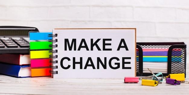 На светлом деревянном фоне калькулятор, разноцветные палочки и записная книжка с текстом внести изменение. бизнес-концепция