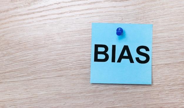 На светлом деревянном фоне - голубой квадратный стикер с надписью bias.