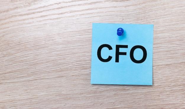 На светлом деревянном фоне - голубая квадратная наклейка с текстом cfo chief financial officer.