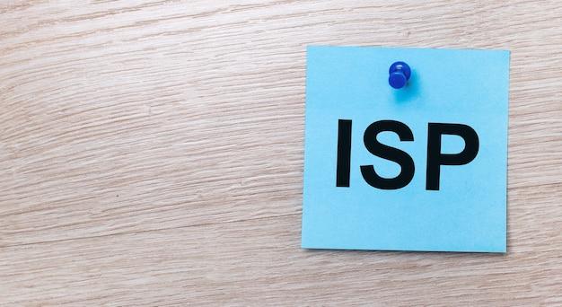 На светлом деревянном фоне - голубая квадратная наклейка с текстом isp internet service provider.