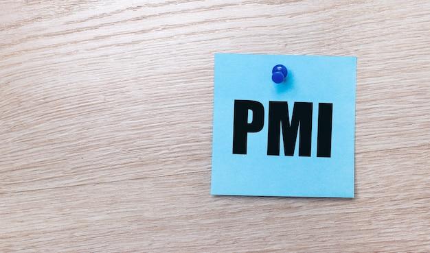 На светлом деревянном фоне - голубая квадратная наклейка с текстом pmi project management institute.