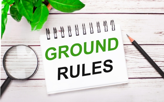 明るい木の背景に、虫眼鏡、鉛筆、緑の植物、白いノートに「groundrules」と書かれています。ビジネスコンセプト