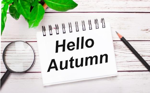На светлом деревянном фоне увеличительное стекло, карандаш, зеленое растение и белый блокнот с текстом привет осень. бизнес-концепция