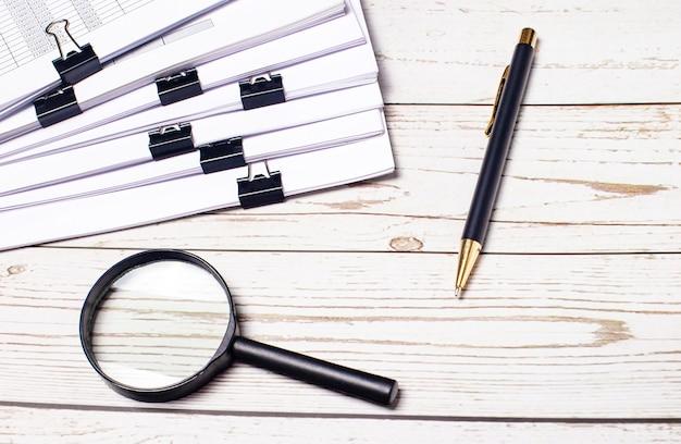 明るい木の背景に、虫眼鏡、紙のクリップの下にある書類とペン。職場のクローズアップ。ビジネスコンセプト