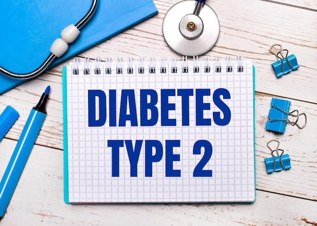 明るい木製の背景に、聴診器、青いメモ帳、青いペーパークリップ、青いマーカー、2型糖尿病のテキストが書かれた1枚の紙。医療コンセプト