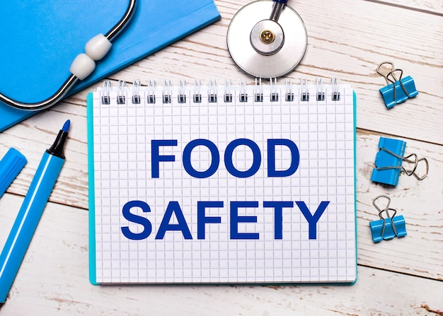 밝은 나무 배경에 청진기, 파란색 메모장, 파란색 종이 클립, 파란색 마커 및 food safety라는 텍스트가 있는 종이. 의료 개념