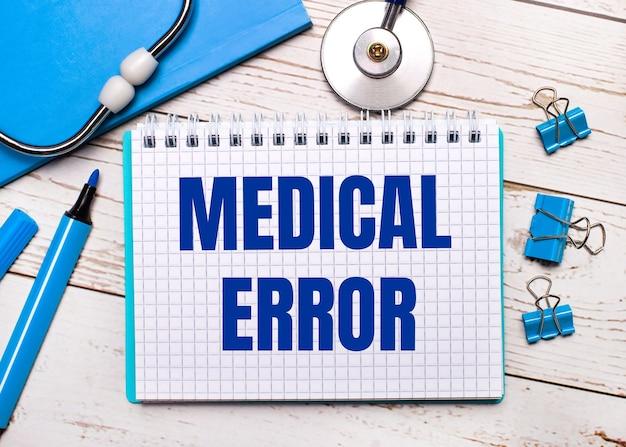 明るい木製の背景に、聴診器、青いメモ帳、青いペーパークリップ、青いマーカー、および医療過誤のテキストが記載された1枚の紙。医療コンセプト