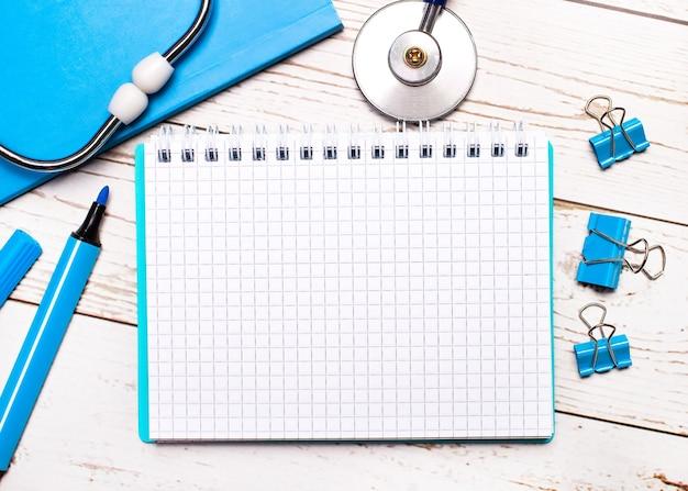 На светлом деревянном фоне стетоскоп, блокнот, скрепки, маркер и лист бумаги с местом для вставки текста. медицинская концепция