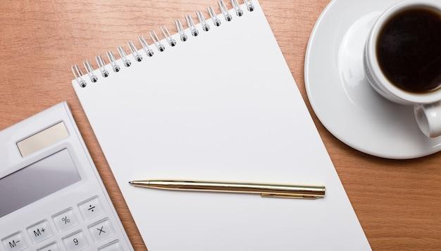 明るい木の背景に、白い一杯のコーヒー、白い電卓、金色のペン、テキストを挿入する場所のある空白のノートブック。テンプレート。ビジネスコンセプト