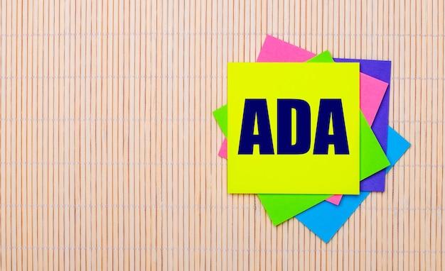 明るい木製の背景に、ada americans with disabilitiesactというテキストが付いた明るい色とりどりのステッカー