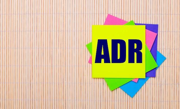 На светлом деревянном фоне яркие разноцветные наклейки с текстом adr alternative dispute resolution.