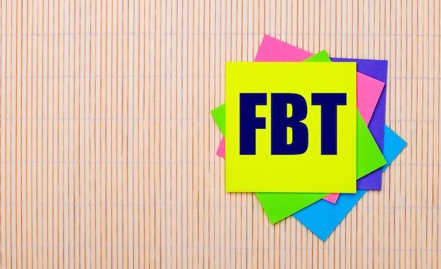 밝은 나무 배경에 fbt fringe benefit tax라는 텍스트가 있는 밝은 다색 스티커