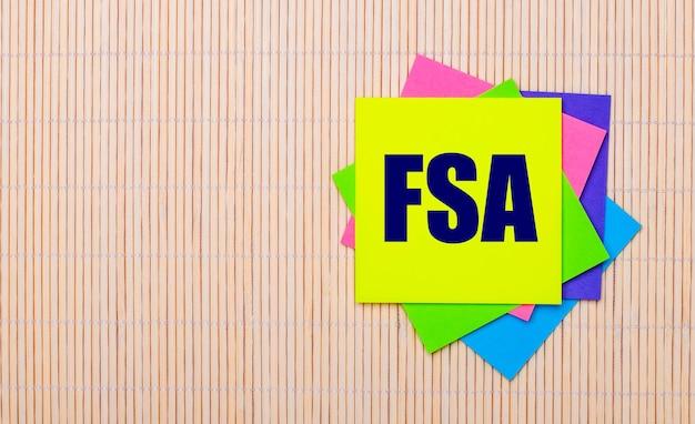 На светлом деревянном фоне яркие разноцветные наклейки с текстом fsa flexible spending account.
