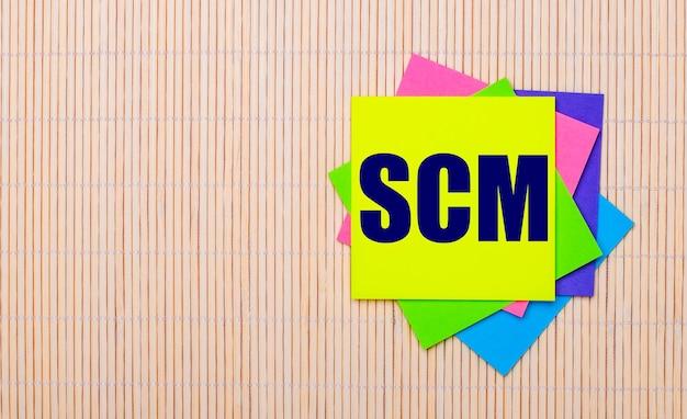 На светлом деревянном фоне яркие разноцветные наклейки с текстом scm supply chain management.
