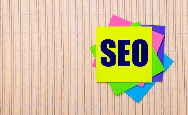 На светлом деревянном фоне яркие разноцветные наклейки с текстом seo search engine optimization.