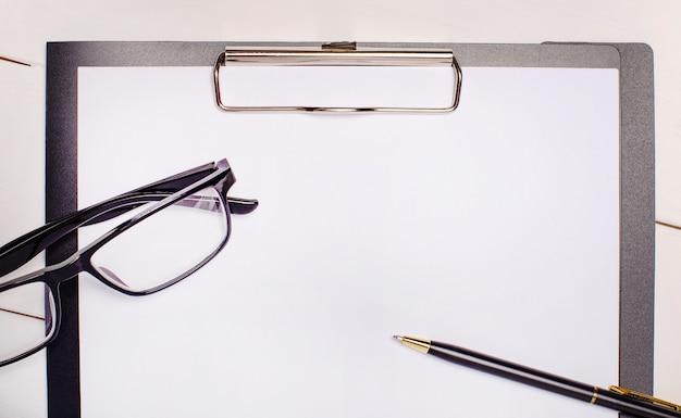 明るい木の背景に、眼鏡、ペン、テキストを挿入する場所のある紙。テンプレート。ビジネスコンセプト