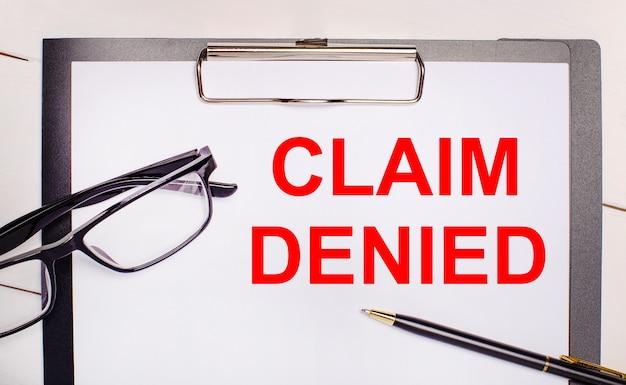 На светлом деревянном фоне очки, ручка и лист бумаги с текстом претензия отказана. бизнес-концепция Premium Фотографии