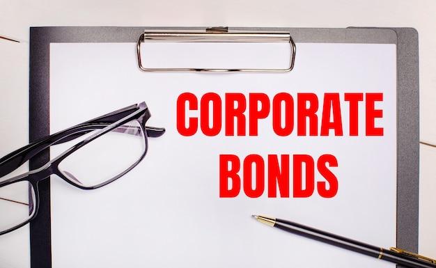 На светлом деревянном фоне очки, ручка и лист бумаги с текстом corporate bonds. бизнес-концепция