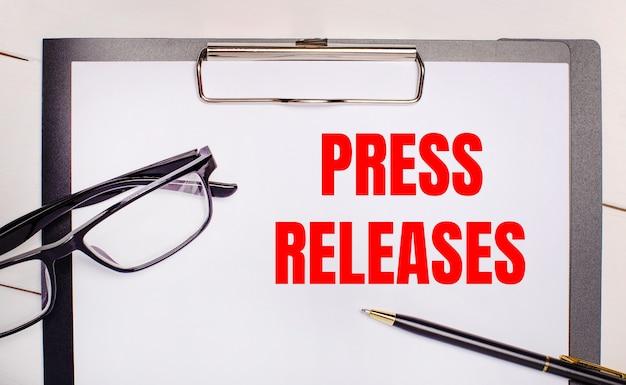 На светлом деревянном фоне очки, ручка и лист бумаги с текстом пресс-релизы. бизнес-концепция