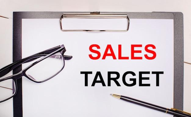 明るい木製の背景のメガネに、ペンと1枚の紙に「salestarget」というテキストが表示されます。ビジネスコンセプト