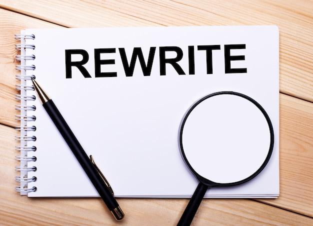明るい木製の背景に、ペン、虫眼鏡、「rewrite」というテキストのノートがあります。