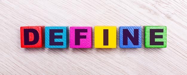 На светлом деревянном фоне разноцветные деревянные кубики с надписью define.