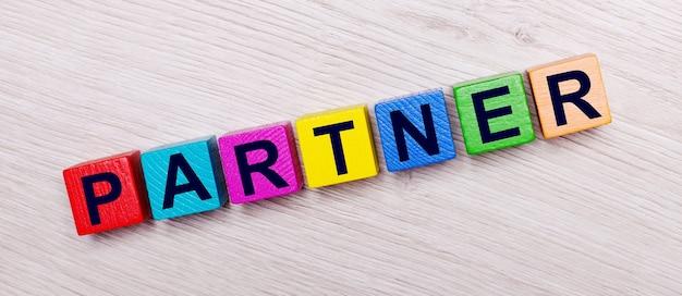 На светлом деревянном фоне на разноцветных ярких деревянных кубиках слово партнер