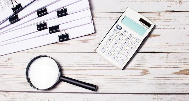 На светлом деревянном фоне бумаги белый калькулятор и увеличительное стекло. бизнес-концепция