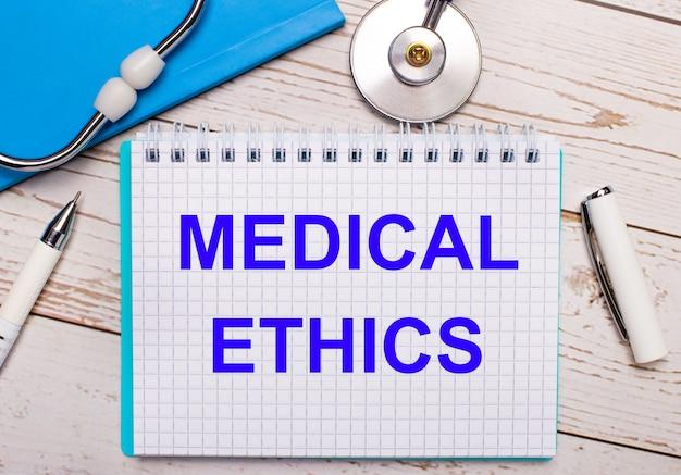 明るい木製の背景には、聴診器、青いノート、白いペン、そして「医療倫理」というテキストが書かれた一枚の紙があります。医療コンセプト
