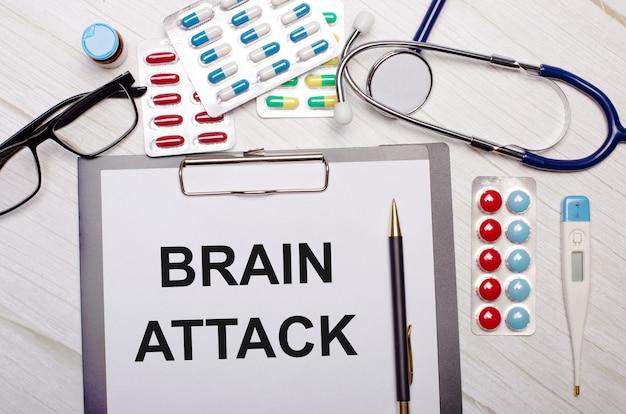 На светлом деревянном фоне бумага с надписью brain attack, стетоскоп, разноцветные таблетки, очки и ручка. медицинская концепция