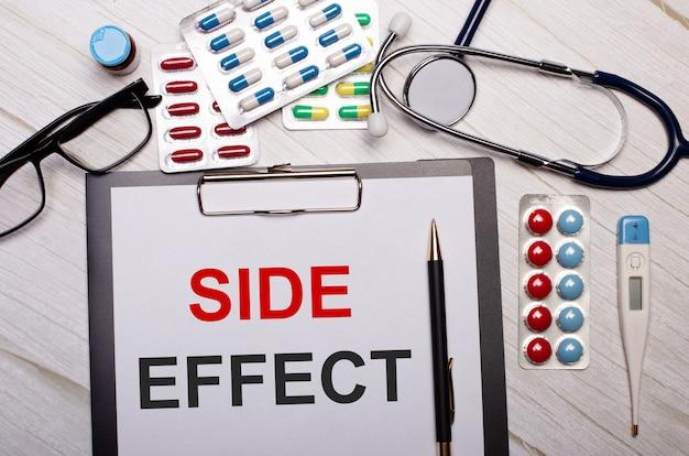 На светлом деревянном фоне - бумага с надписью побочный эффект, стетоскоп, разноцветные таблетки, очки и ручка. медицинская концепция