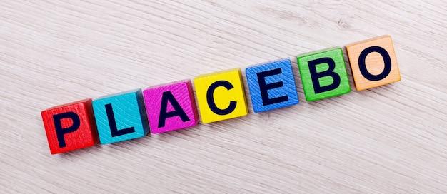 マルチカラーの明るい木製の立方体の明るい木製の表面にプラセボという言葉