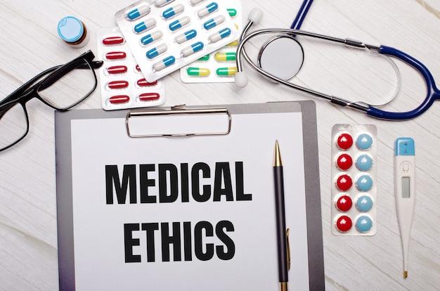 明るい木の表面には、医療倫理の碑文が書かれた紙、聴診器、カラフルな錠剤、眼鏡、ペンがあります