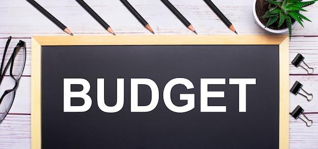 На светлом деревянном столе - доска с текстом бюджет, карандаши, растения, стаканы и скрепки. бизнес-концепция