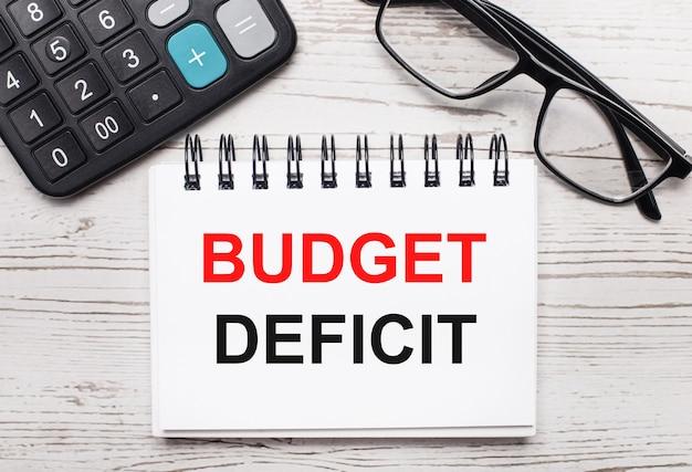 На светлом деревянном столе калькулятор, очки и пустой блокнот с текстом дефицит бюджета. бизнес-концепция
