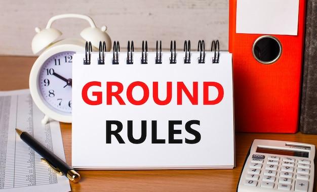 На светлом деревянном столе калькулятор, очки и пустой блокнот с надписью общие правила. бизнес-концепция