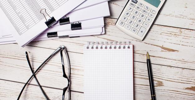 明るい木製のテーブルには、書類、眼鏡、電卓、ペン、ノートがあります。ビジネスコンセプト