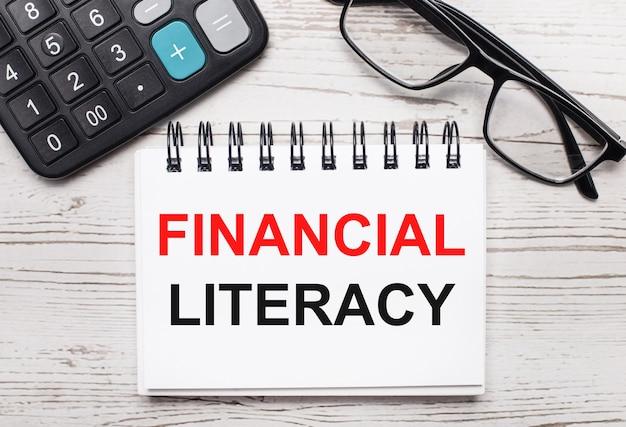 밝은 나무 테이블 계산기, 안경, financial literacy라는 텍스트가 있는 빈 메모장. 비즈니스 개념
