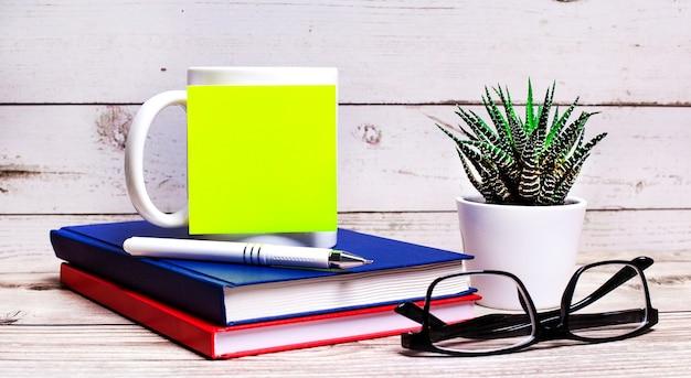 На светлом деревянном столе лежат синяя и красная тетрадь, растение в горшке, очки в черной оправе и белая чашка с пустой желтой наклейкой, на которой можно вставить текст. копировать пространство