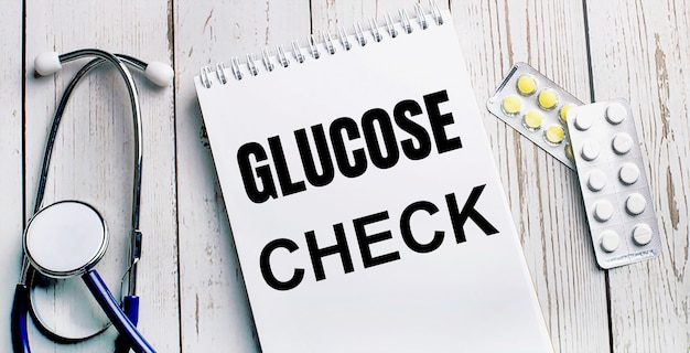 На светлом деревянном столе лежат стетоскоп, таблетки и блокнот с надписью glucose check. медицинская концепция