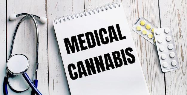 軽い木製のテーブルの上に、聴診器、丸薬、医療大麻の碑文が書かれたノートが置かれています。医療の概念