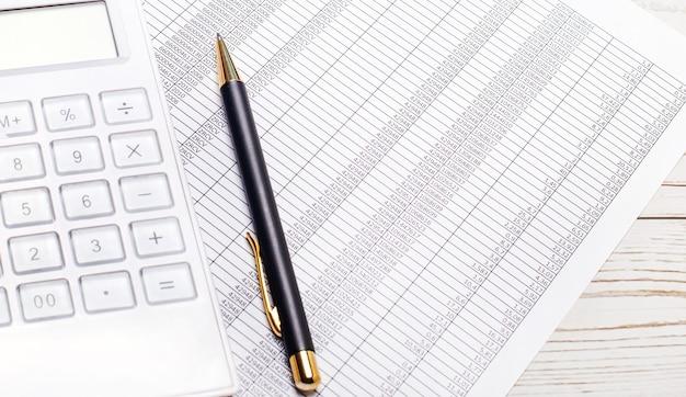На светлом деревянном столе лежат отчеты, белый калькулятор и ручка. бизнес-концепция