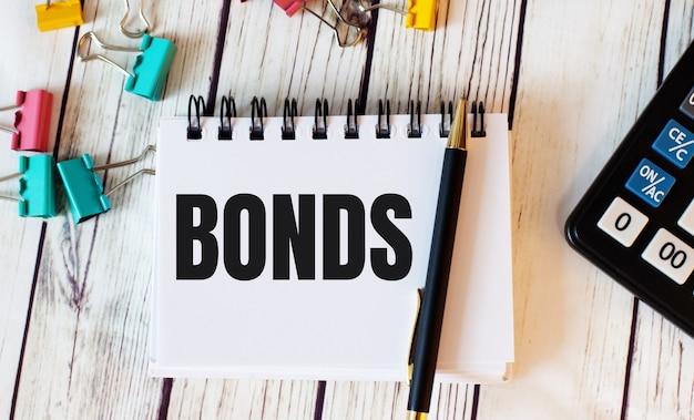 明るい木製のテーブルの上に、電卓、マルチカラーのペーパークリップ、ペンとbondsという単語が書かれたノートがあります。