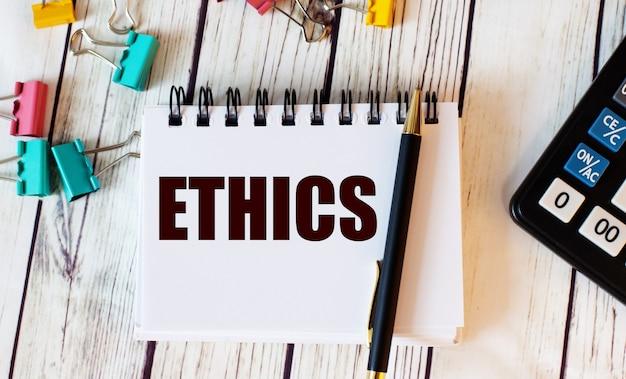가벼운 나무 테이블에는 계산기, 여러 가지 색의 종이 클립, 펜과 ethics라는 단어가있는 노트북이 놓여 있습니다.